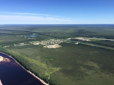 Aerial shot of Fort Albany Ontario showing water green land and the air strip